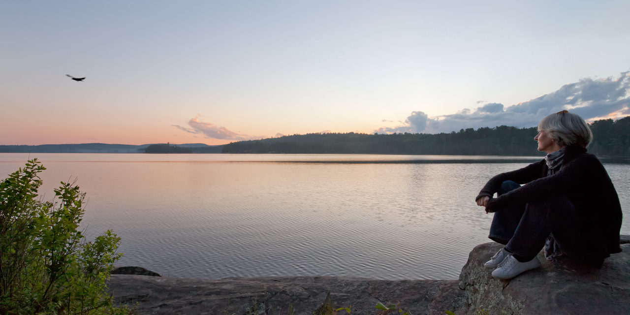 woman and crow watching algonquin park sunset in summer